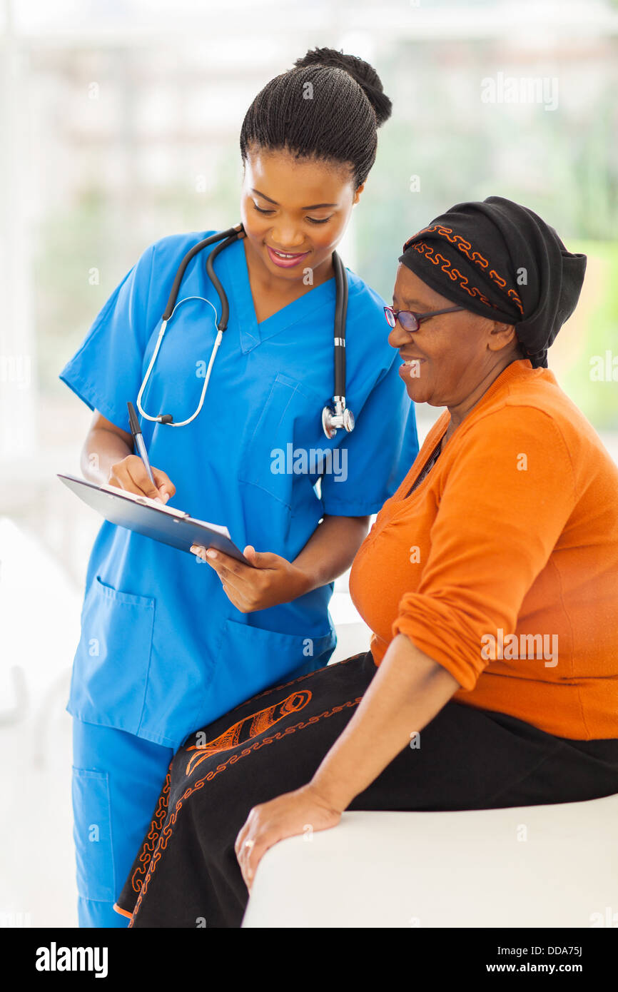 beautiful young African nurse explaining medical test result to senior patient - Stock Image