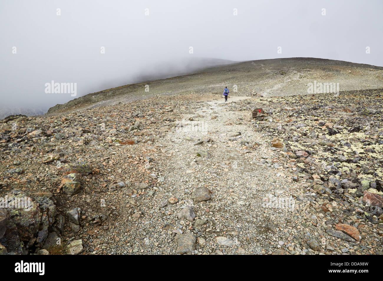 Walker on the Besseggen Ridge walk approaching the bare rocky summit of Veslfjellet shrouded in cloud Jotunheimen Stock Photo