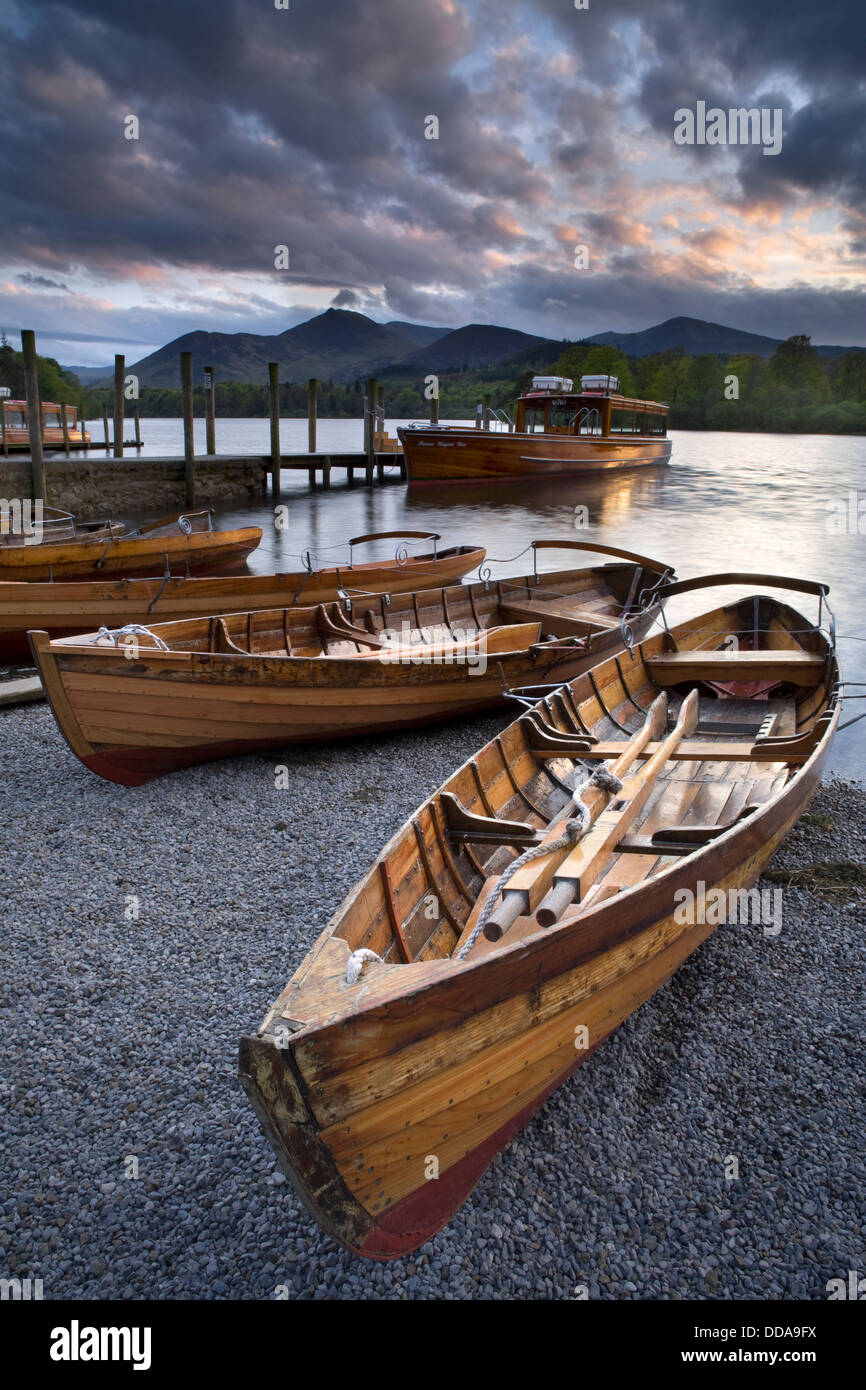 Rowing boats and a cruiser moored up on Derwent Water at sunset with the Catbells in the background, Keswick, Cumbria - Stock Image