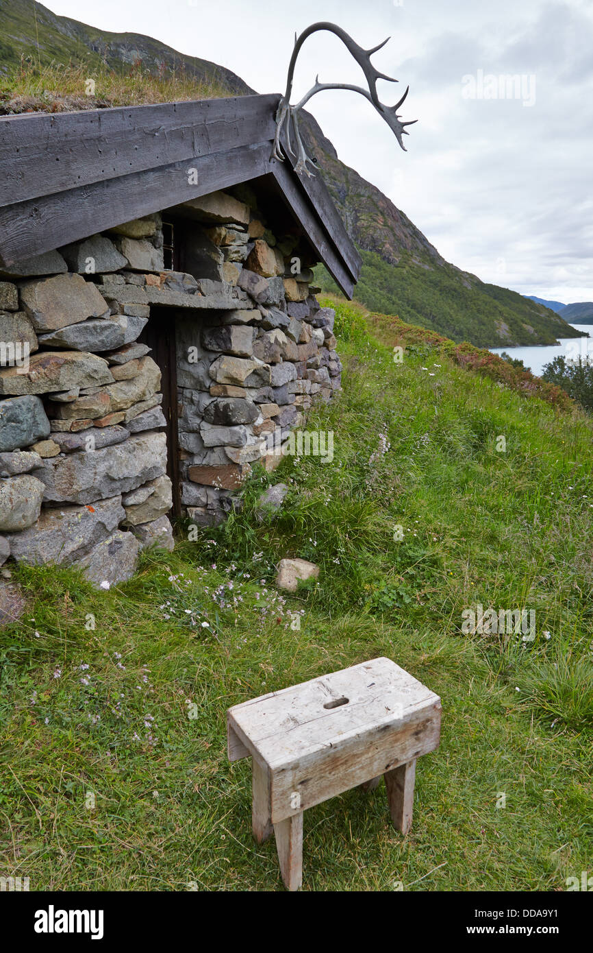Stone cabin by Lake Gjende Jotunheimen National Park with antlers above the door and wooden stool - Stock Image