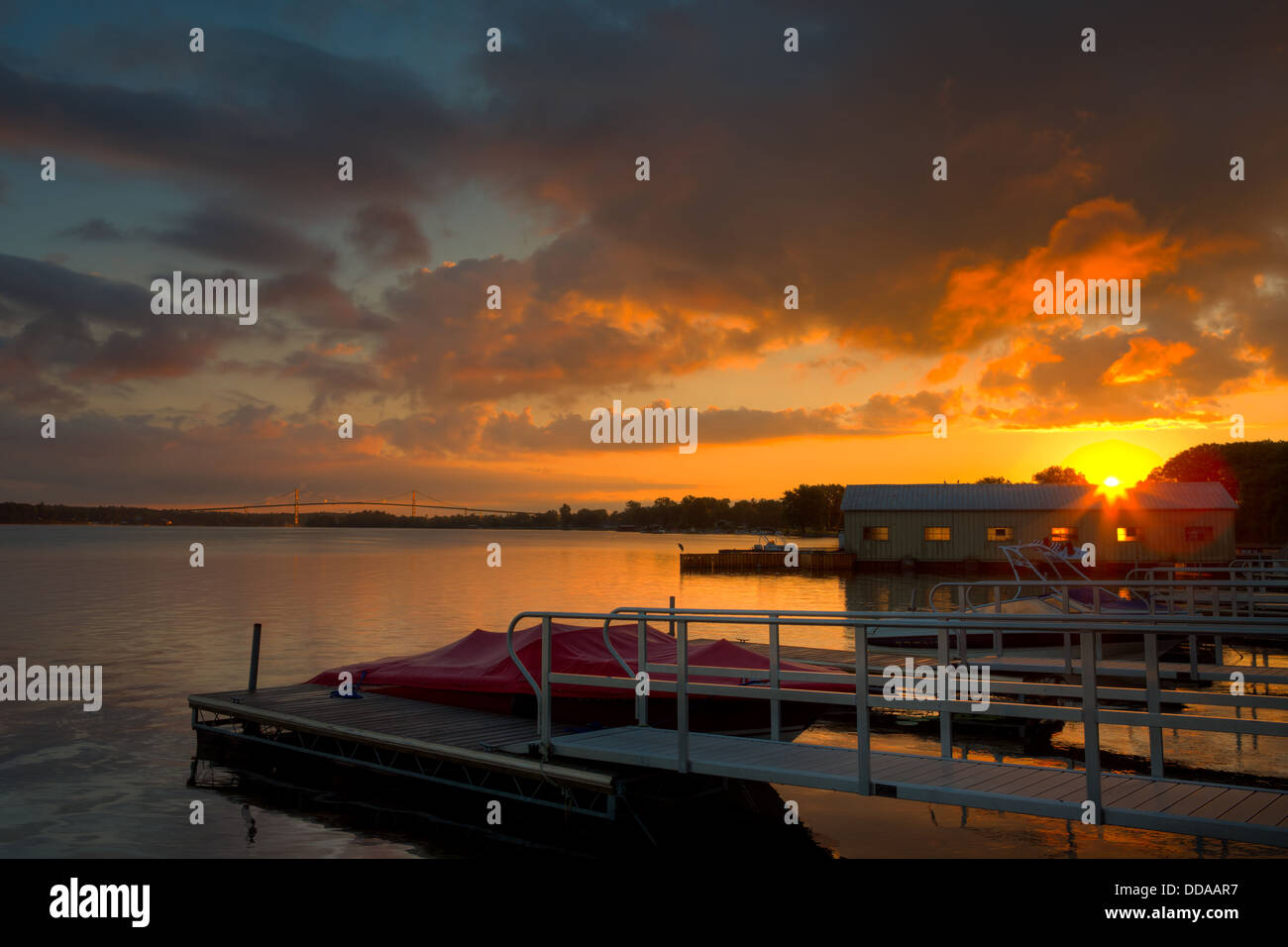 The sun rises over a marina on the Saint Lawrence River with the Thousand Islands Bridge in the background in Alexandria - Stock Image