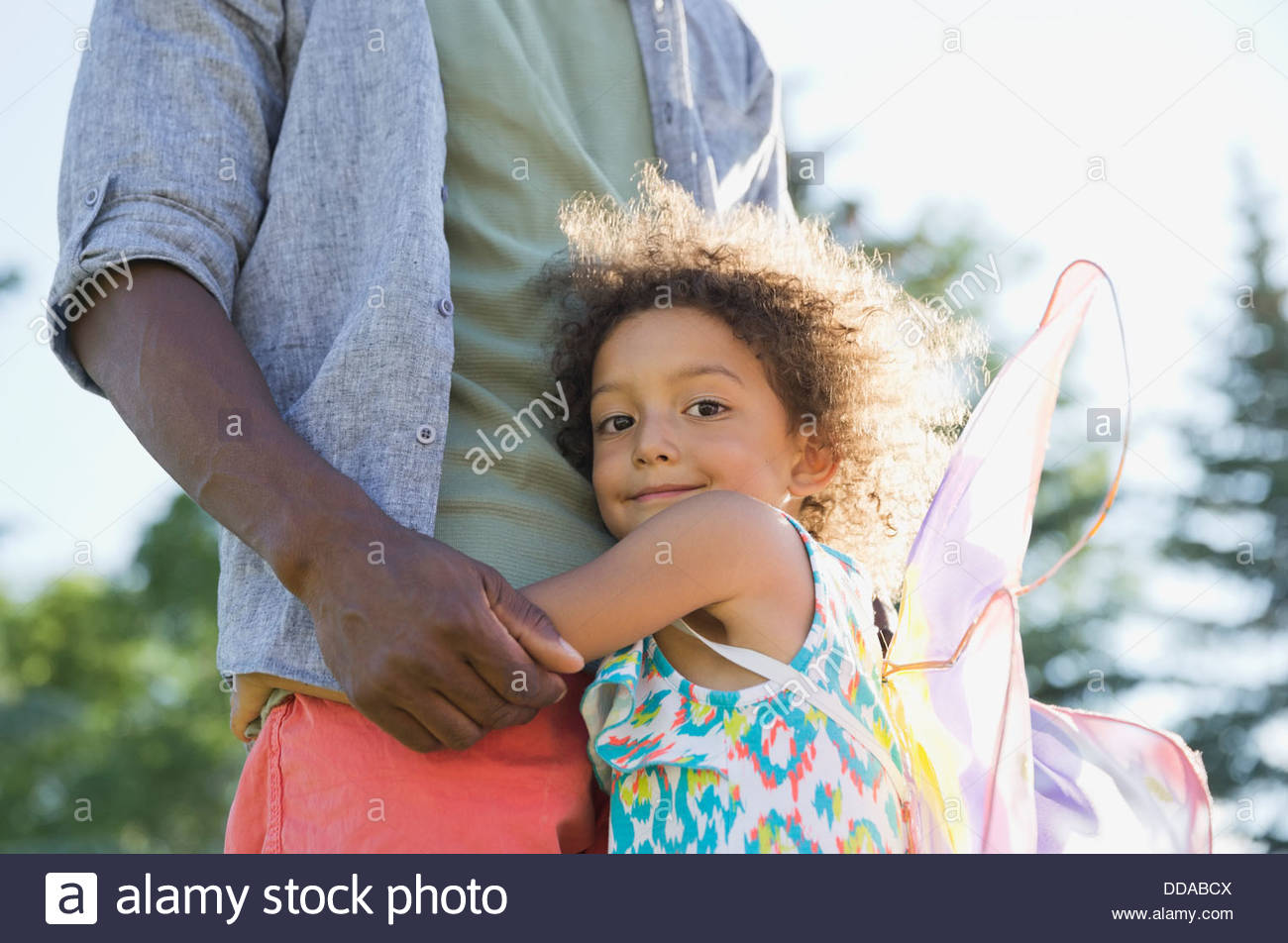 Portrait of cute girl embracing father at park - Stock Image