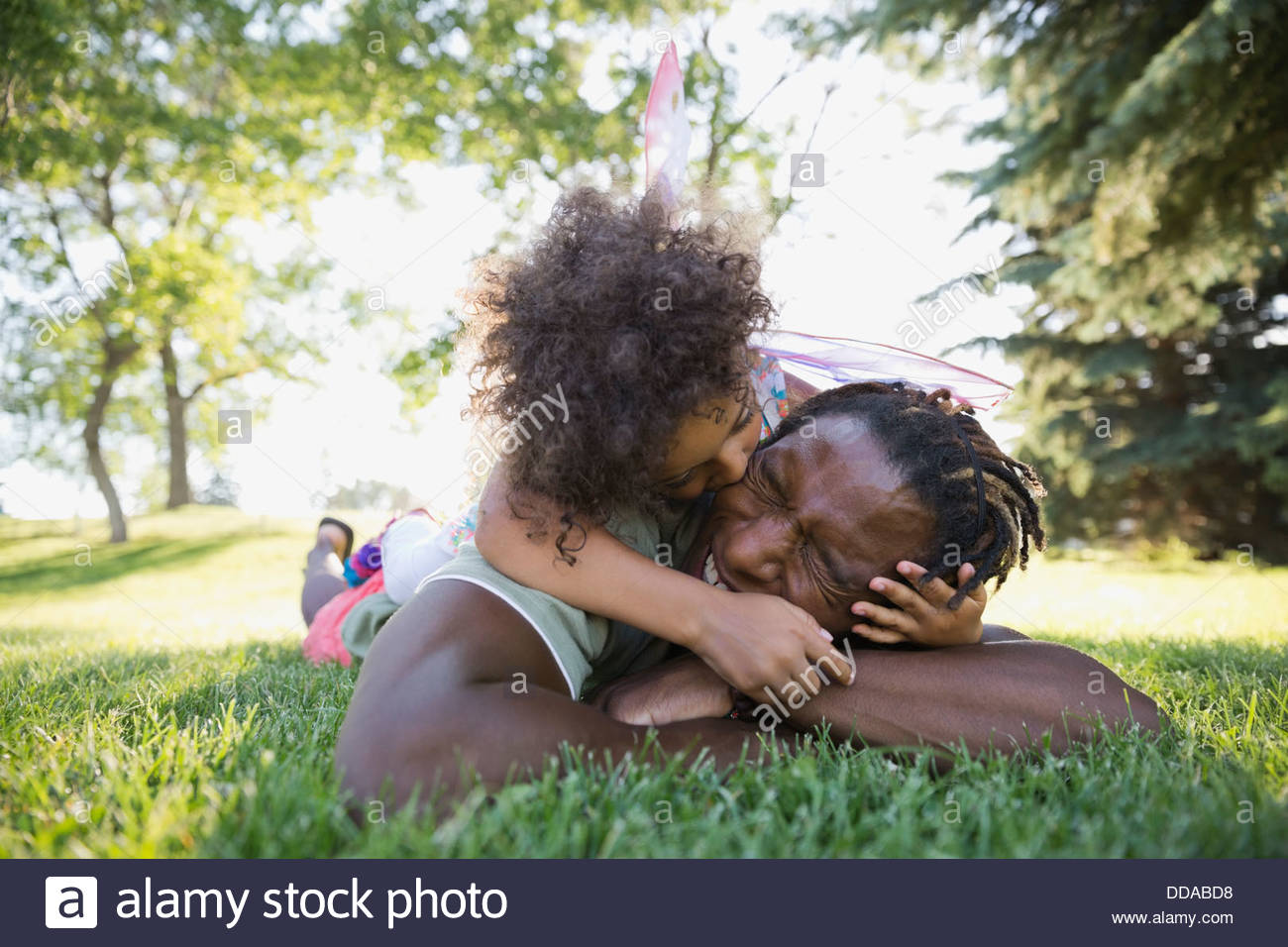 Little girl kissing father playfully - Stock Image