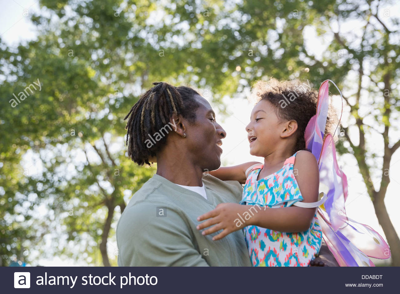 Father and daughter looking at each other in park - Stock Image