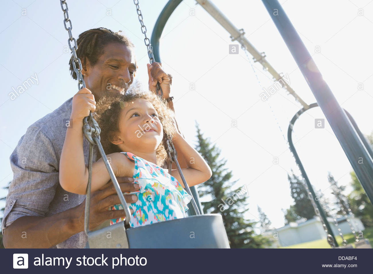 Father pushing daughter on swing Stock Photo