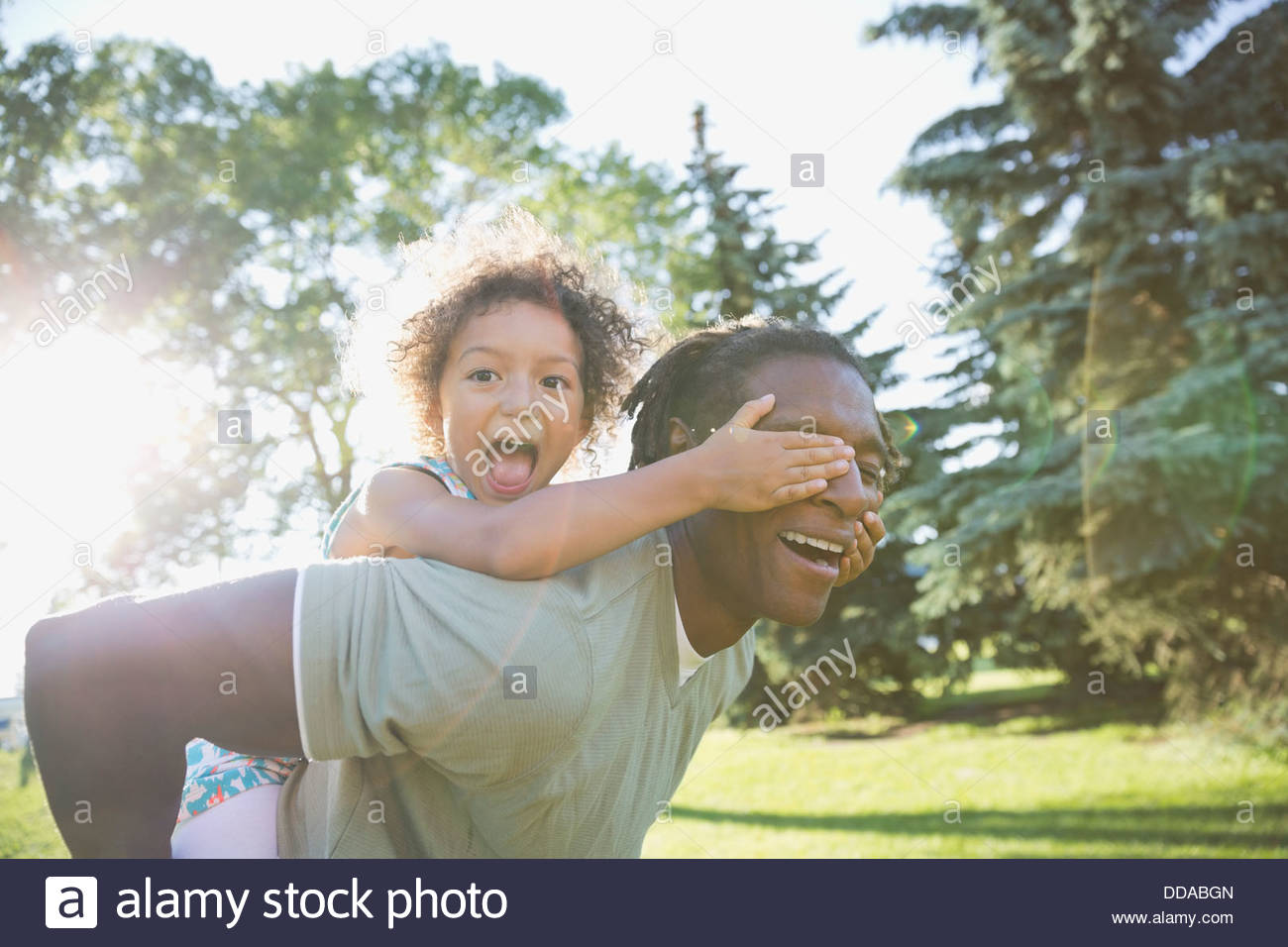 Portrait of playful girl covering fathers eyes in park - Stock Image