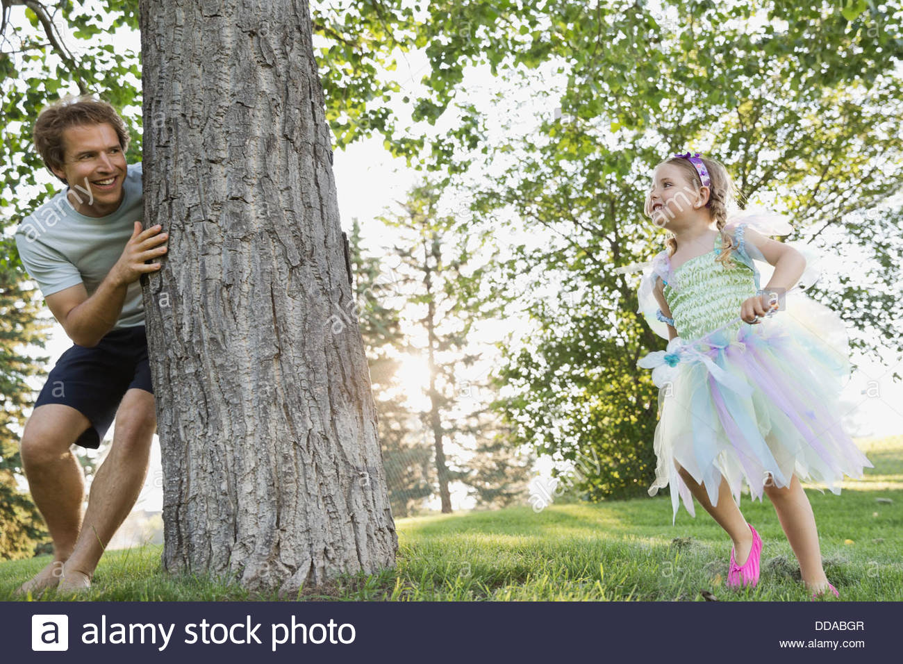 Father and daughter playing hide and seek in park Stock Photo