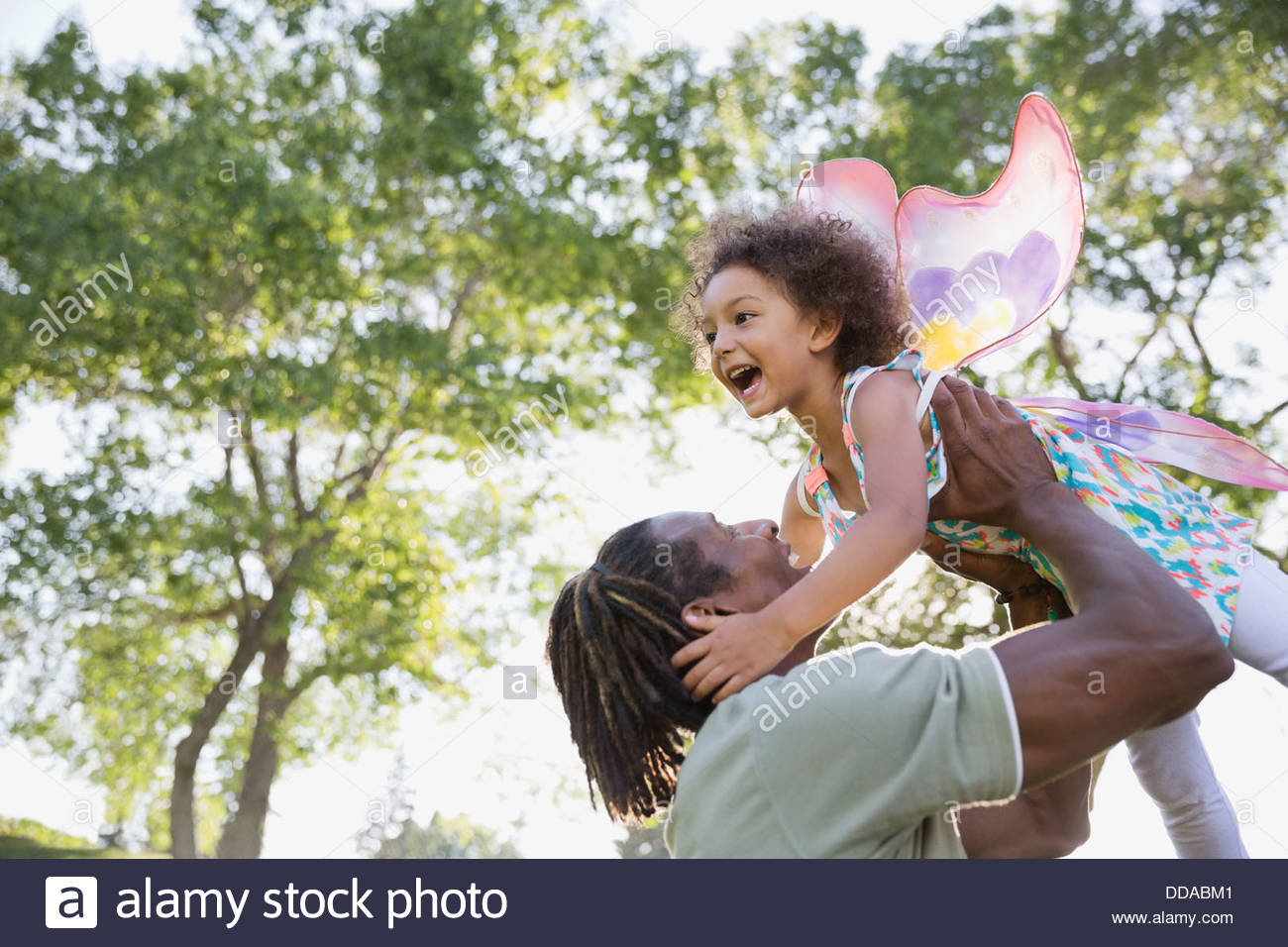 Cheerful man picking up daughter outdoors - Stock Image