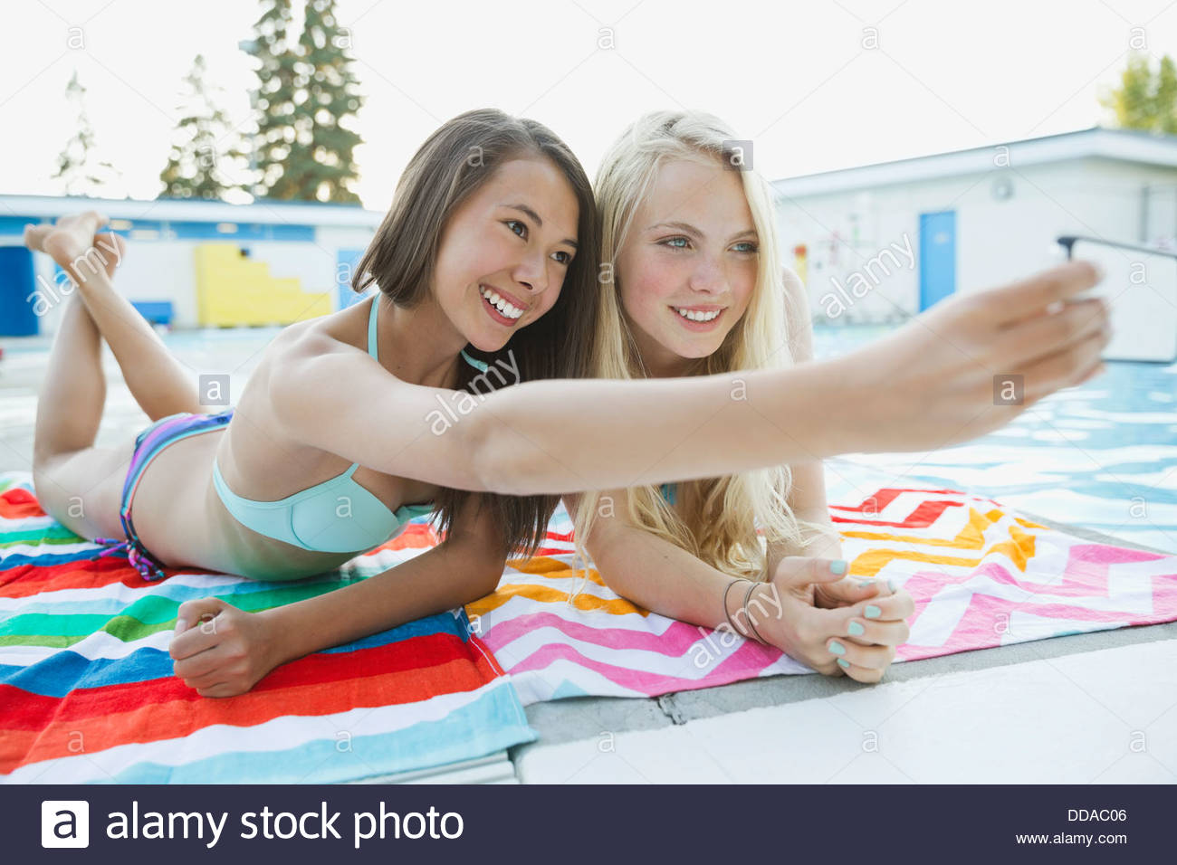 Smiling female friends taking self-portrait by swimming pool - Stock Image