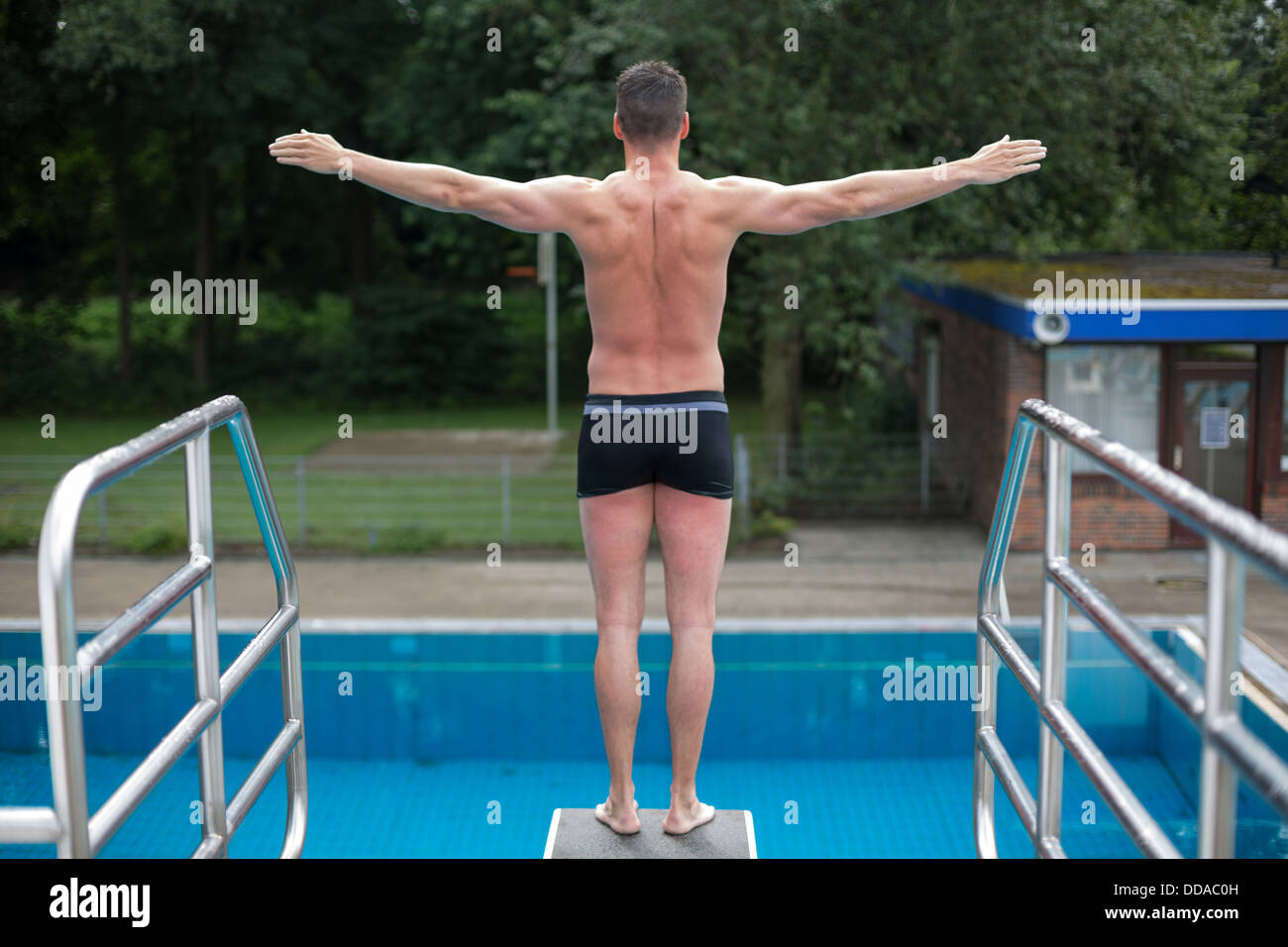 Man standing on diving board at public swimming pool ready to jump ...
