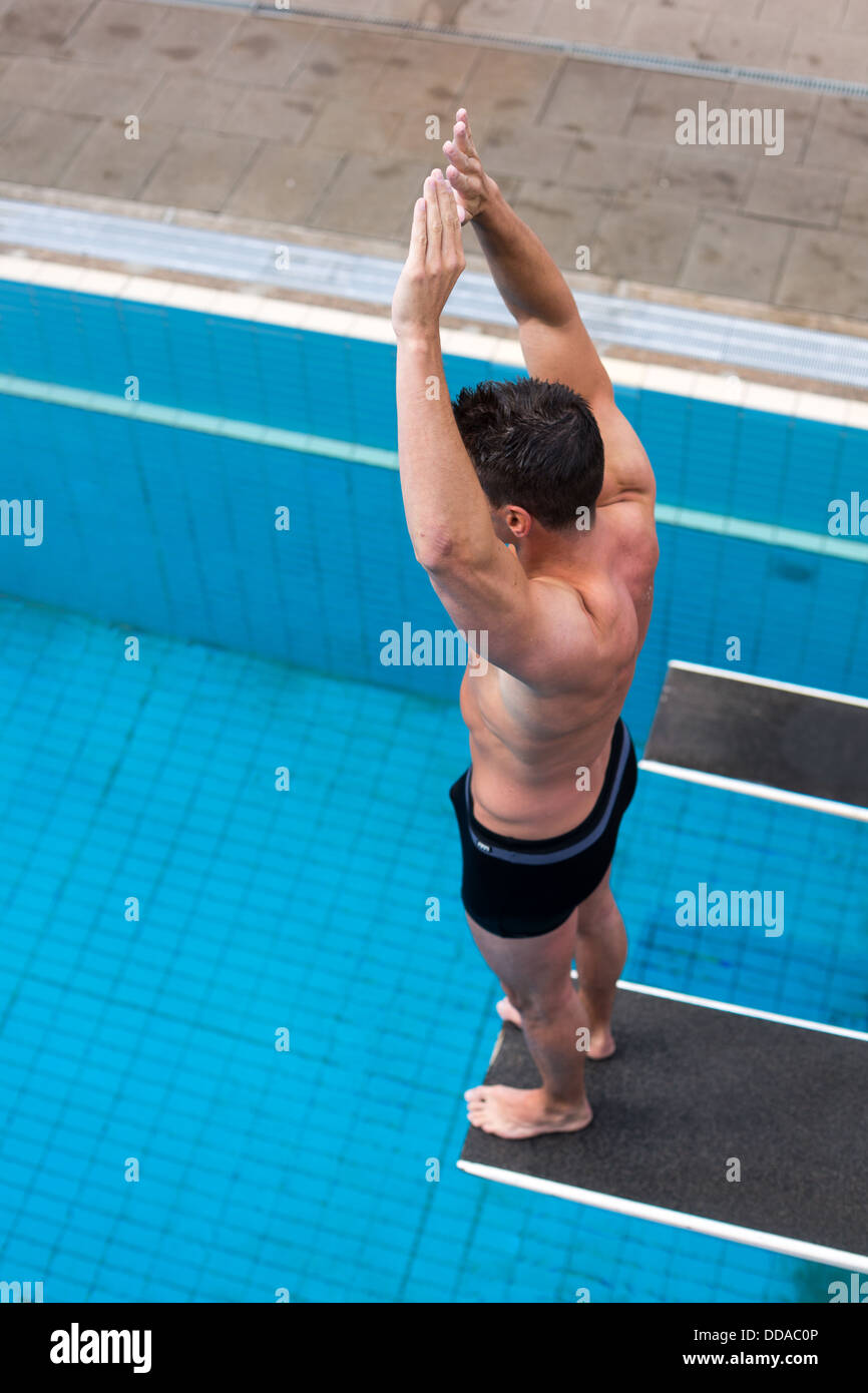 Delightful Man Ready To Jump From Diving Board At Public Swimming Pool
