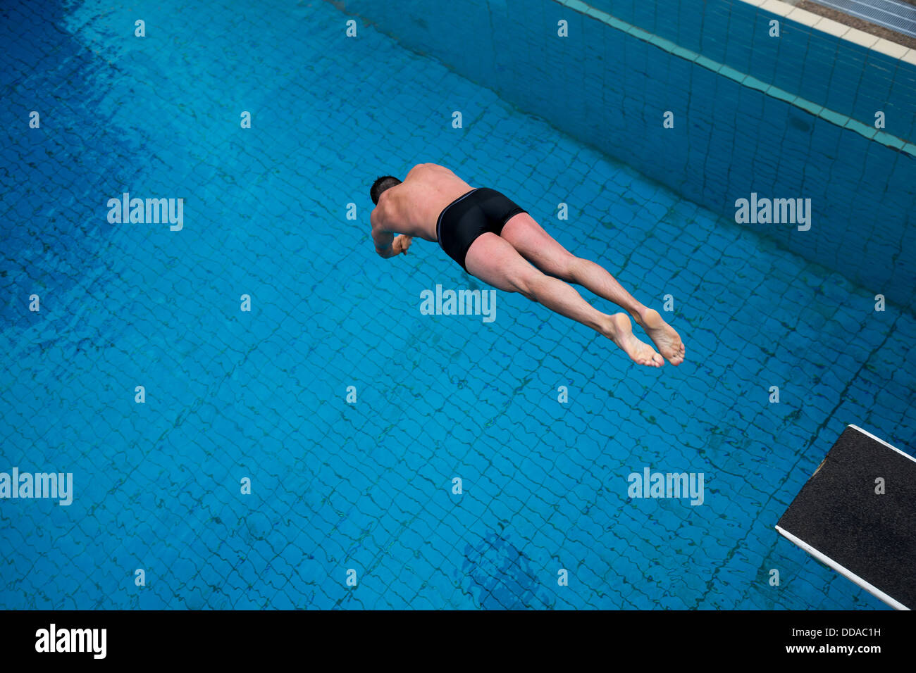 Man jumping from diving board at public swimming pool Stock ...