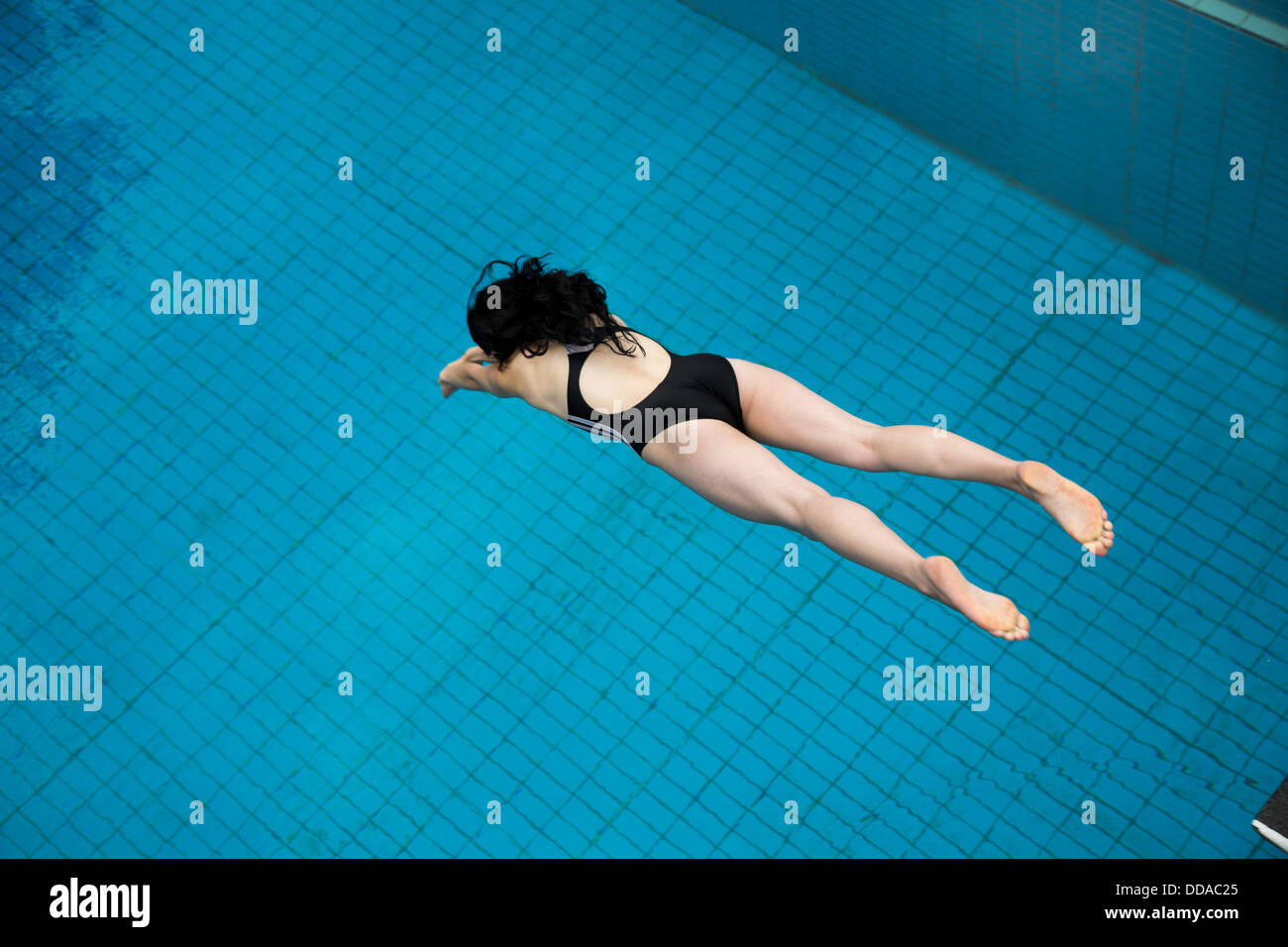 Girl jumping from a spring board at public swimming pool Stock Photo ...
