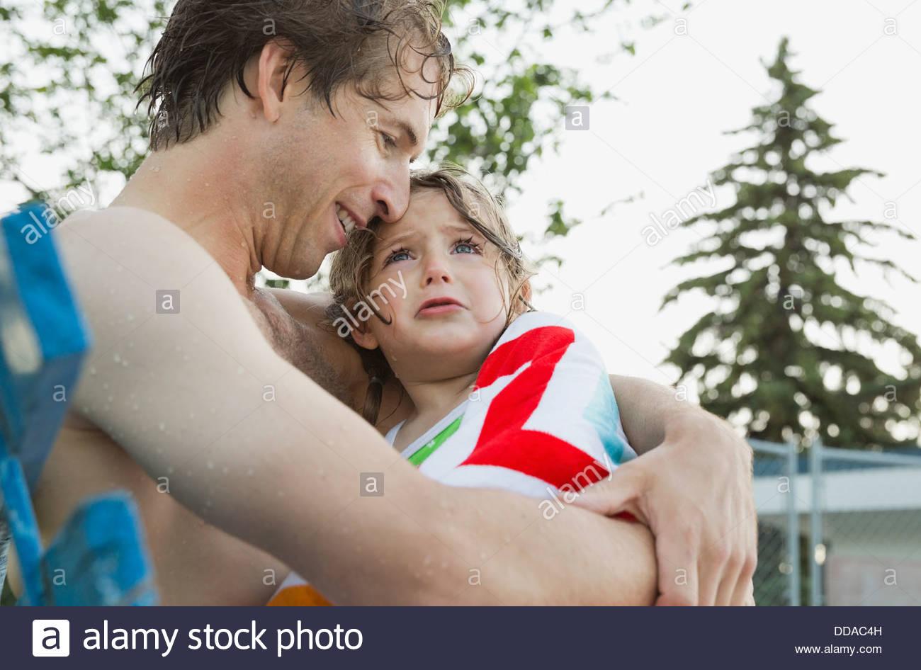 Man consoling crying daughter at swimming pool - Stock Image