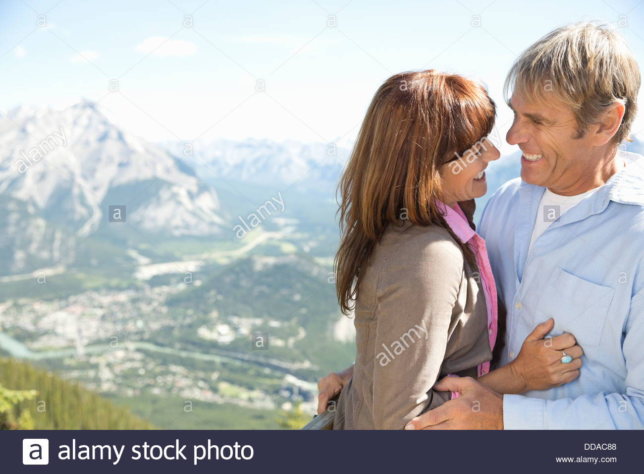 Cheerful mature couple against mountains - Stock Image