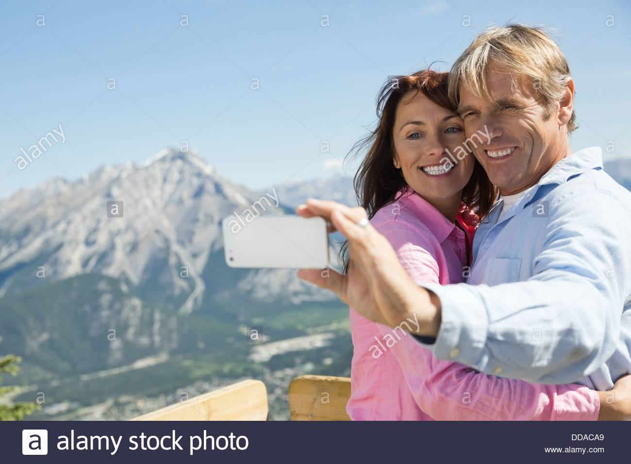 Mature couple taking self-portrait against mountains - Stock Image