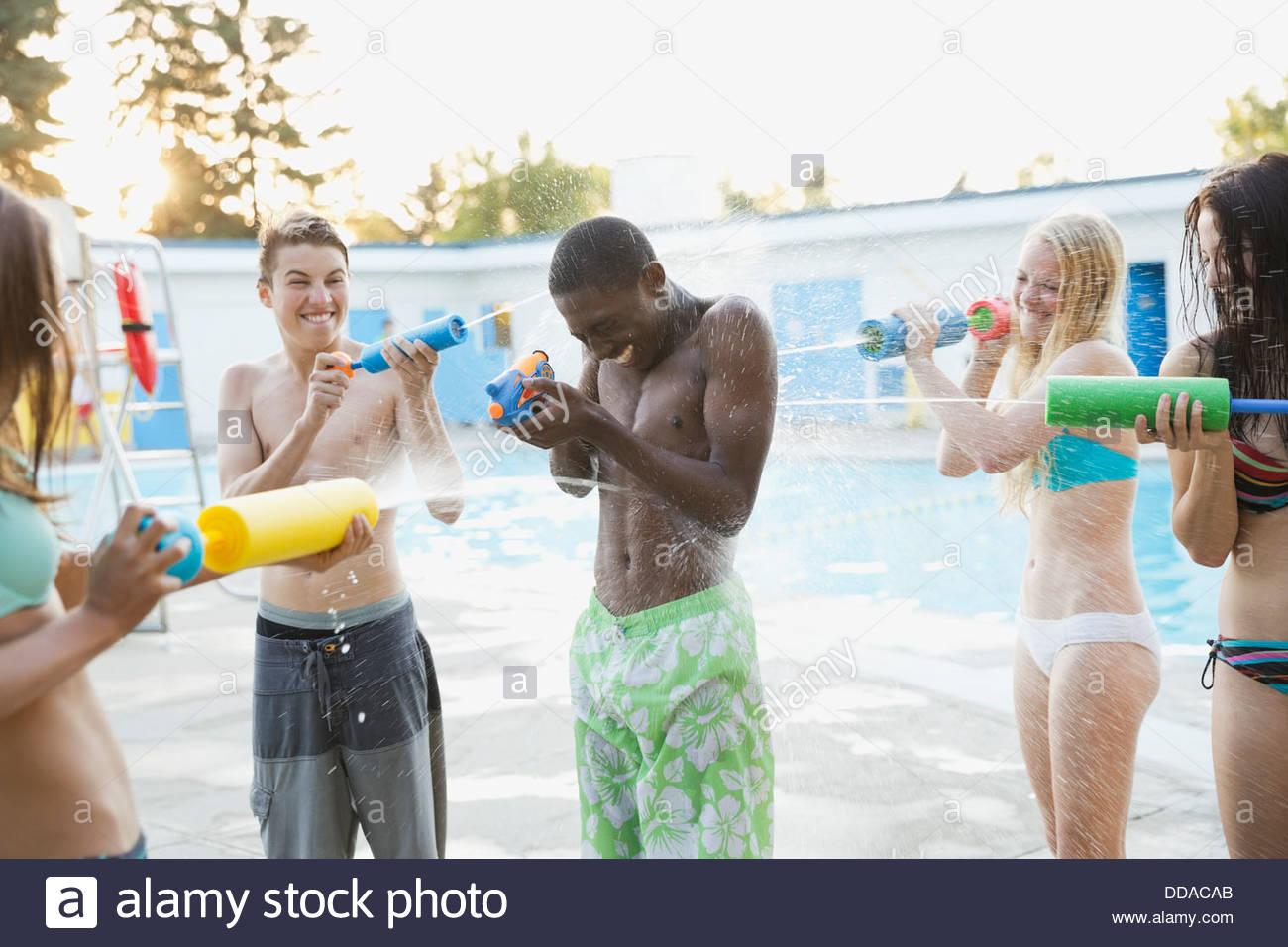 Teenagers having water gun fight by swimming pool - Stock Image