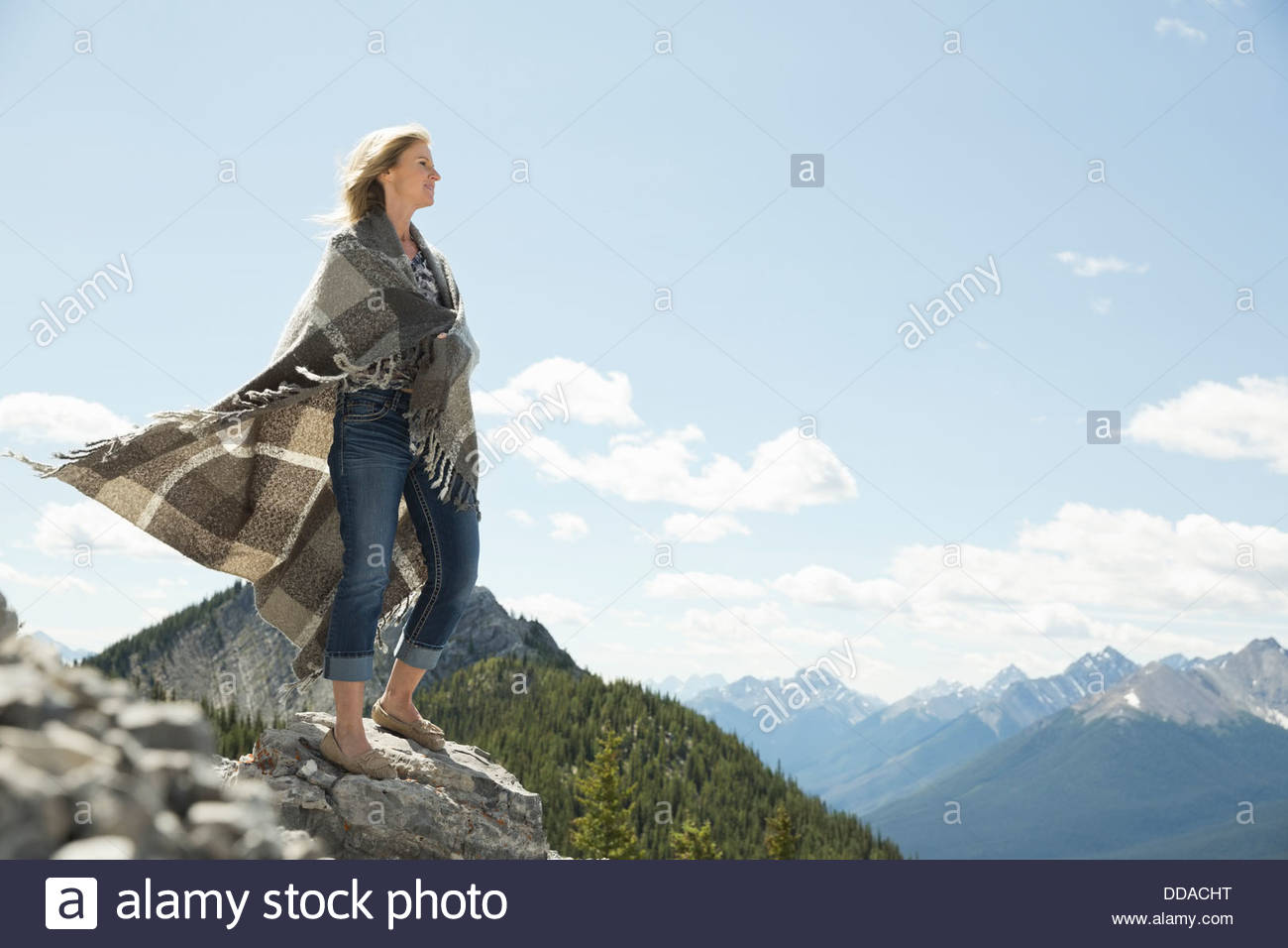 Mature woman wrapped in blanket outdoors - Stock Image