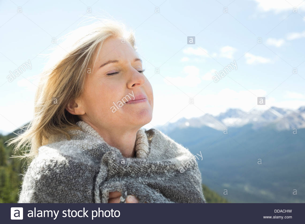 Portrait of woman outdoors with eyes closed - Stock Image