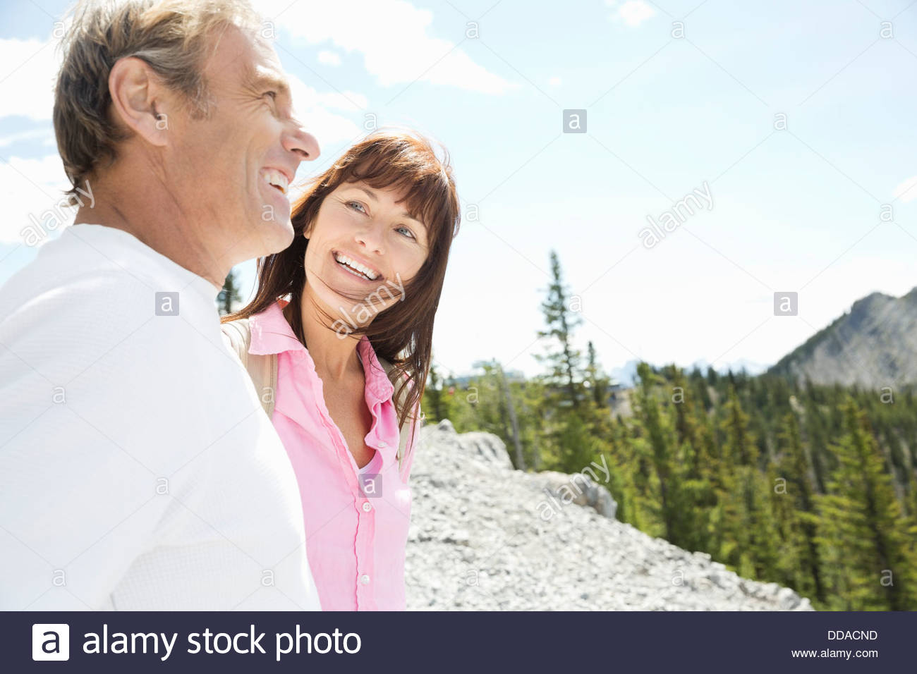 Active couple hiking in mountains - Stock Image