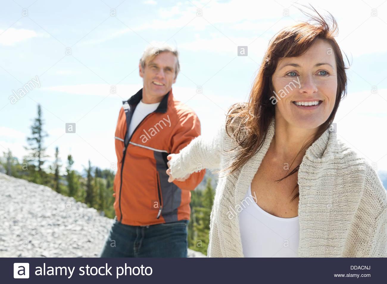 Happy mature couple holding hands on mountain peak - Stock Image