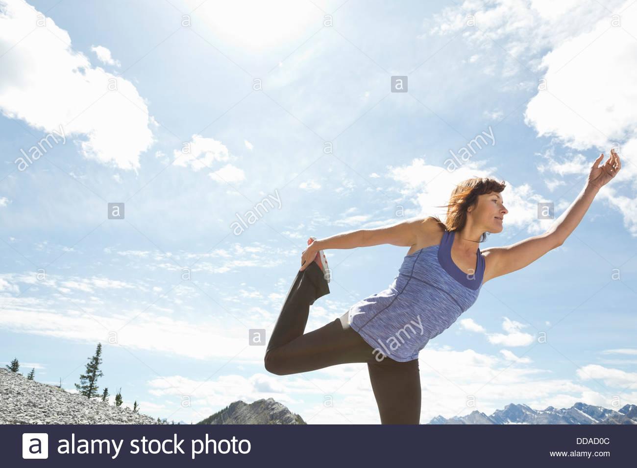 Mature woman practicing yoga on mountaintop Stock Photo