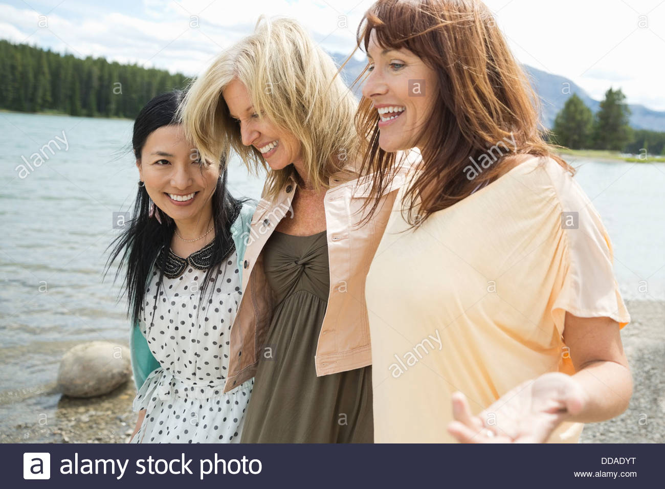 Mature female friends walking on the beach - Stock Image