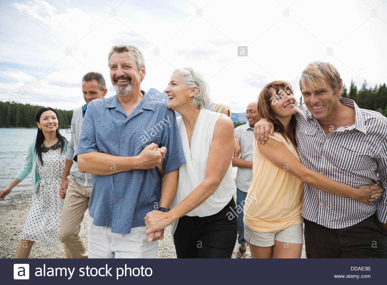 Couples walking along the beach - Stock Image