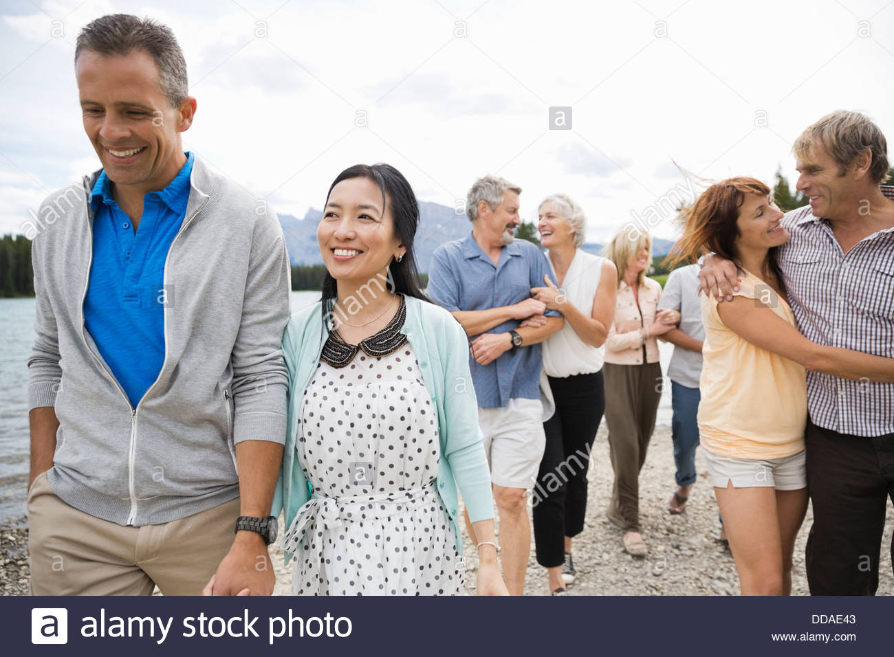 Affectionate couples walking along the beach - Stock Image