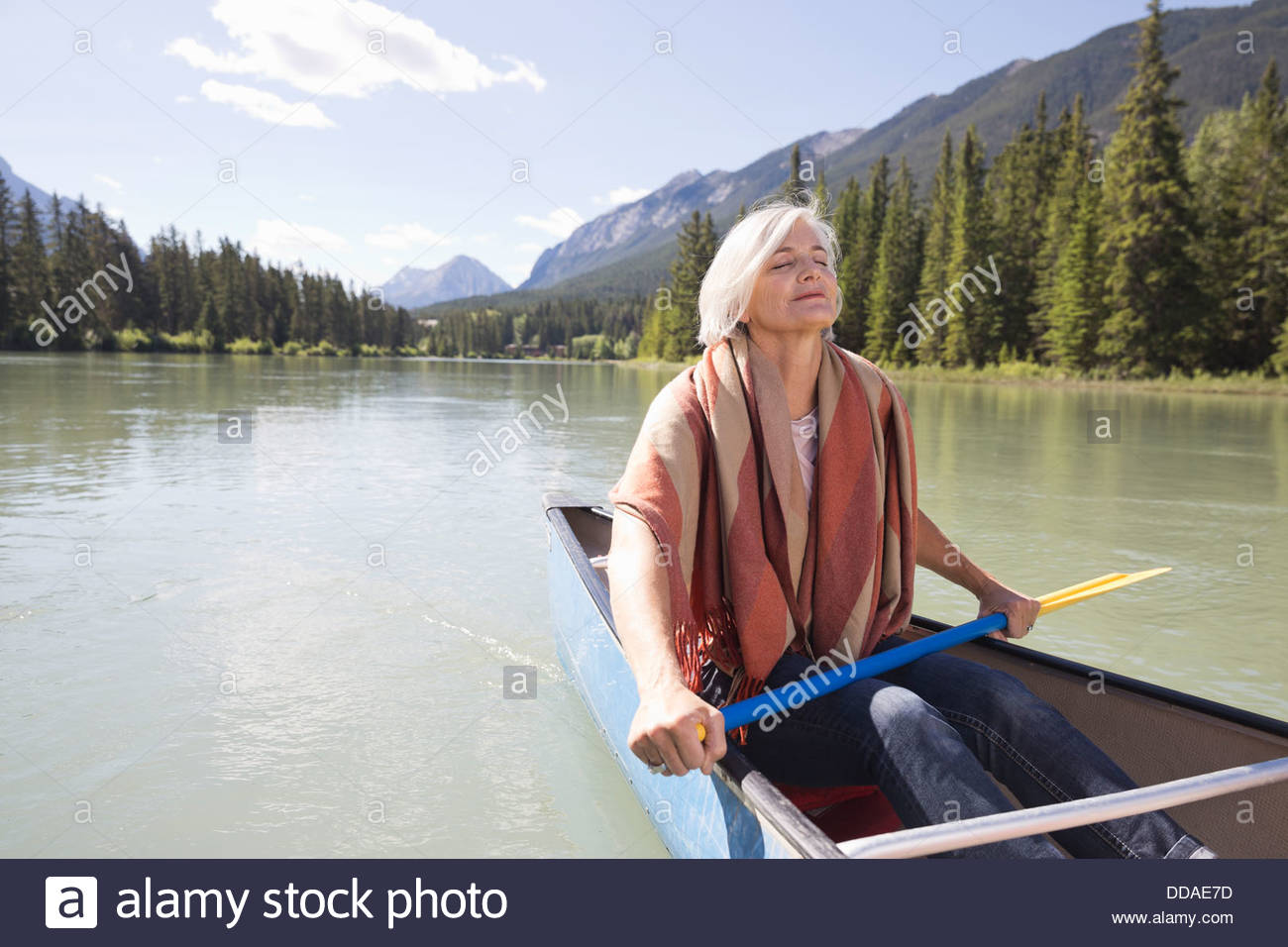 Mature woman relaxing on canoe ride - Stock Image