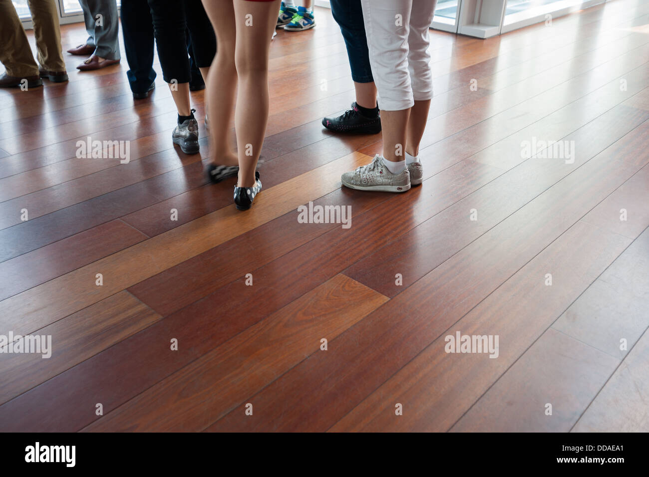 LEGS, PEOPLE STANDING AROUND AT A FUNCTION ON WOODEN FLOOR. ONLY LEGS AND FEET CAN BE SEEN. - Stock Image