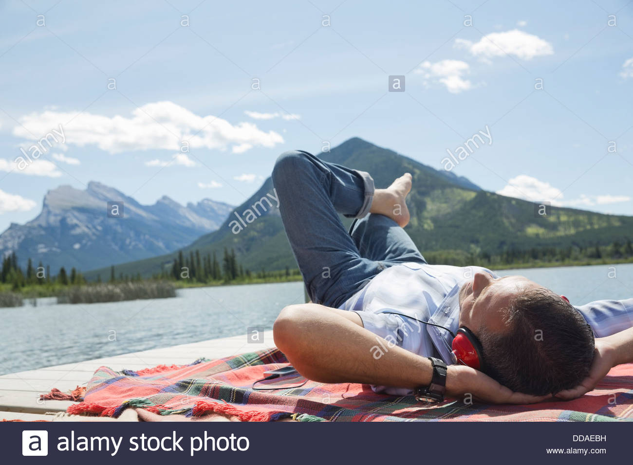 Man relaxing on dock - Stock Image