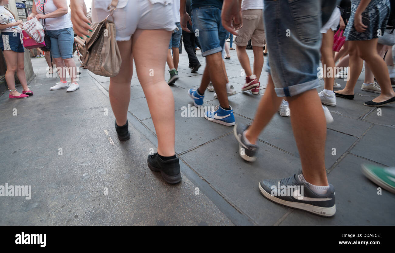 Busy London street as people walk by. No recognizable people, Nike ticks on shoes. - Stock Image