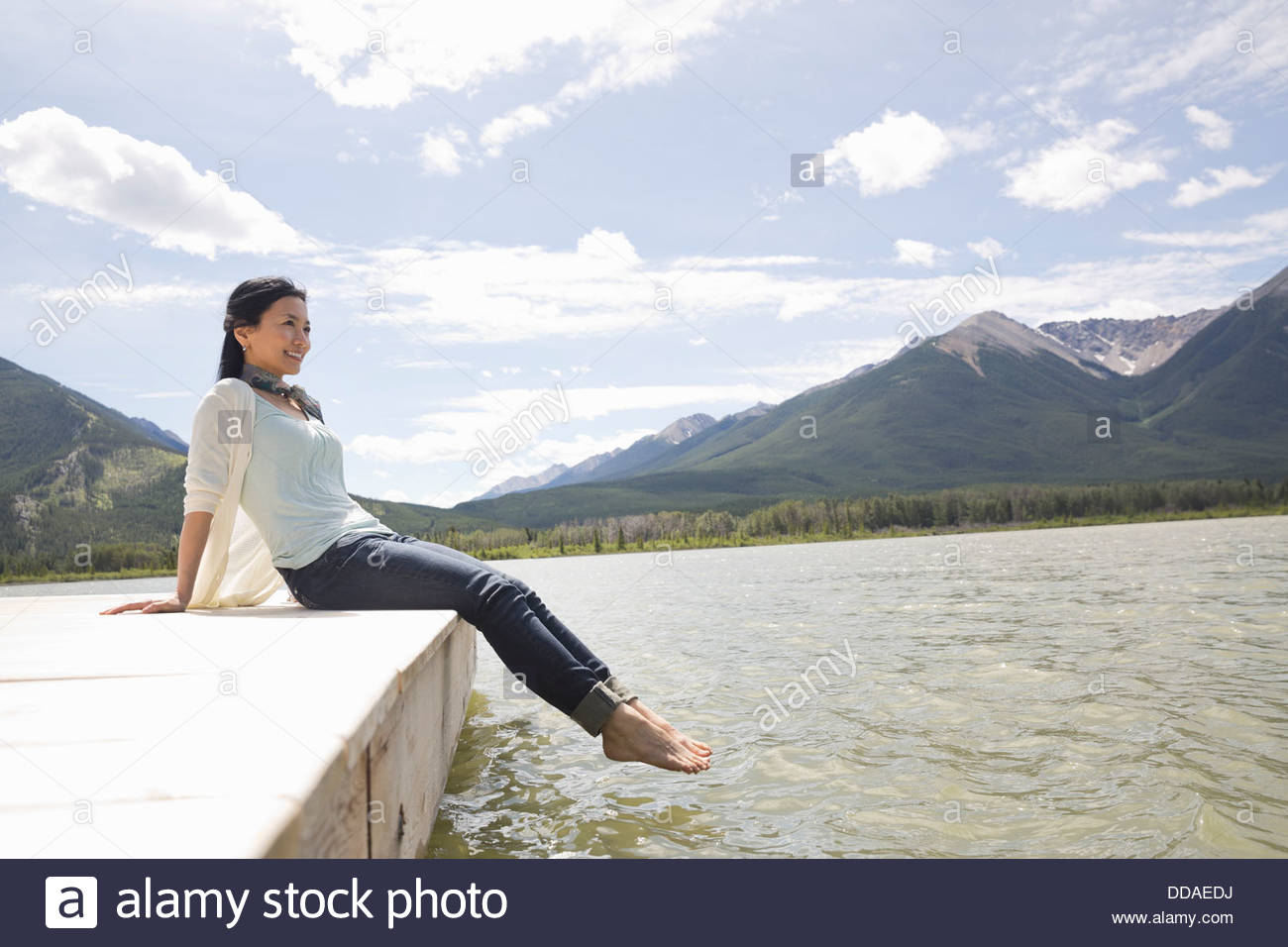 Mature woman enjoying the view from dock - Stock Image