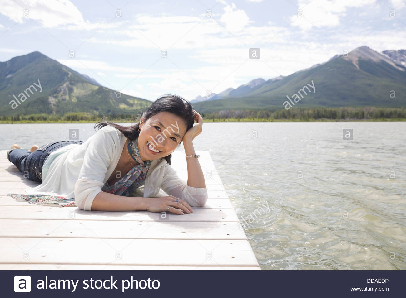 Portrait of mature woman relaxing on dock - Stock Image