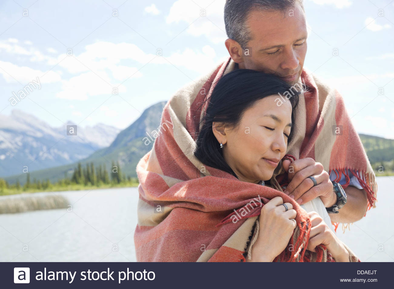 Mature couple wrapped in a blanket - Stock Image