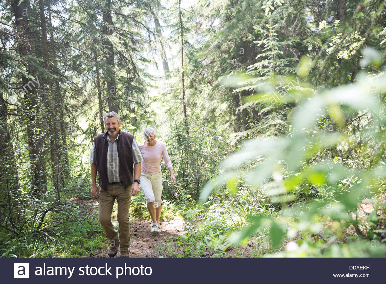 Mature couple hiking through forest - Stock Image