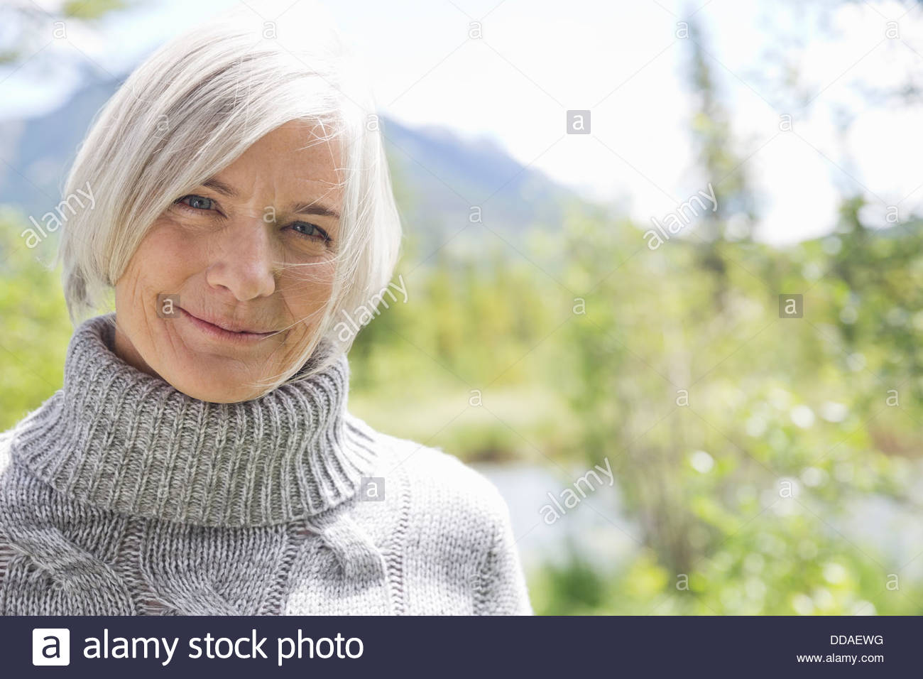 Close-up of mature woman smiling in forest - Stock Image