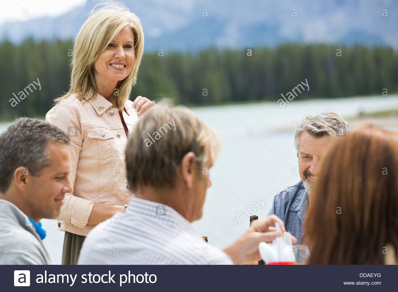 Mature woman socializing with friends outdoors - Stock Image