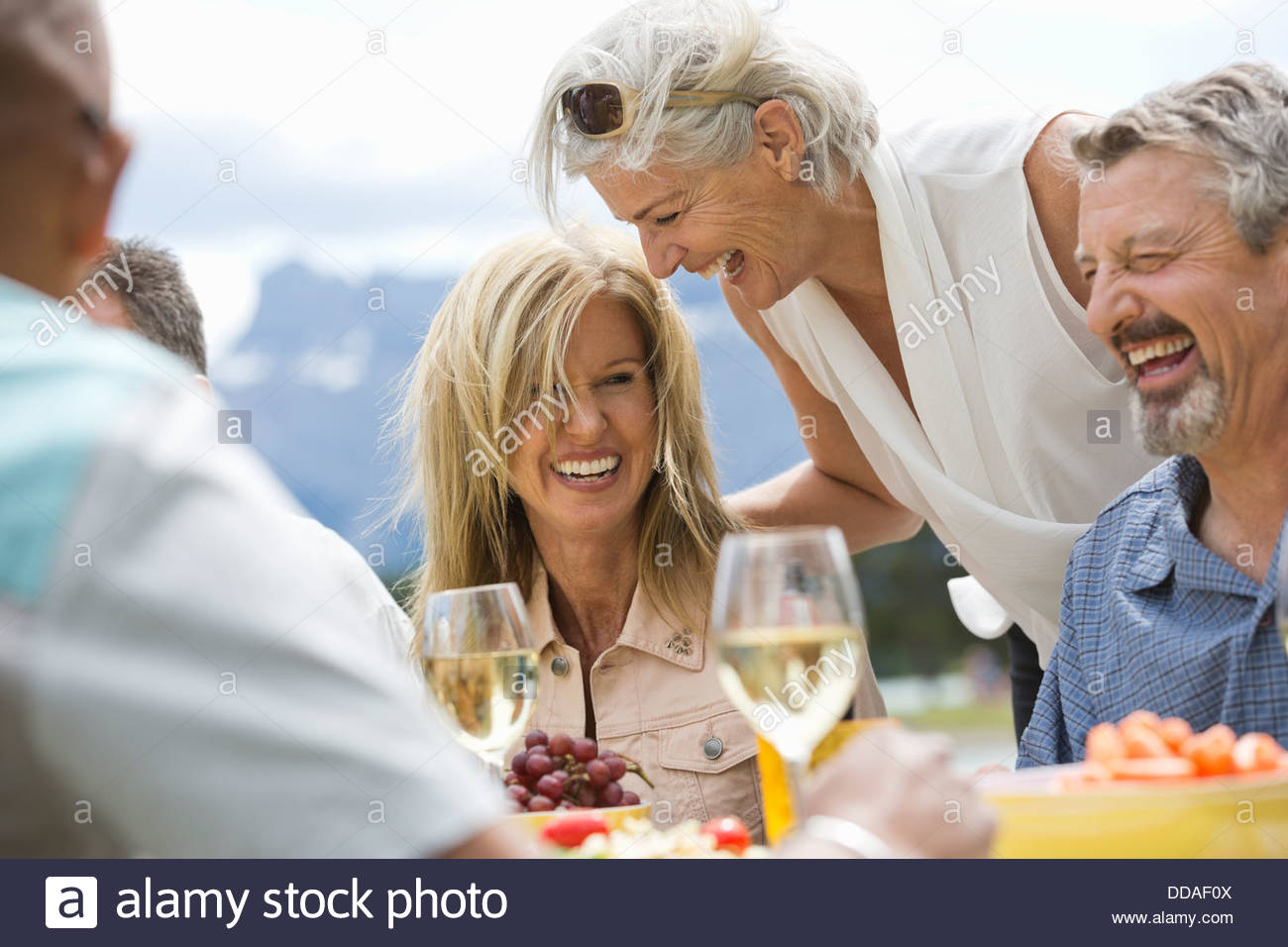 Mature woman laughing with friends - Stock Image