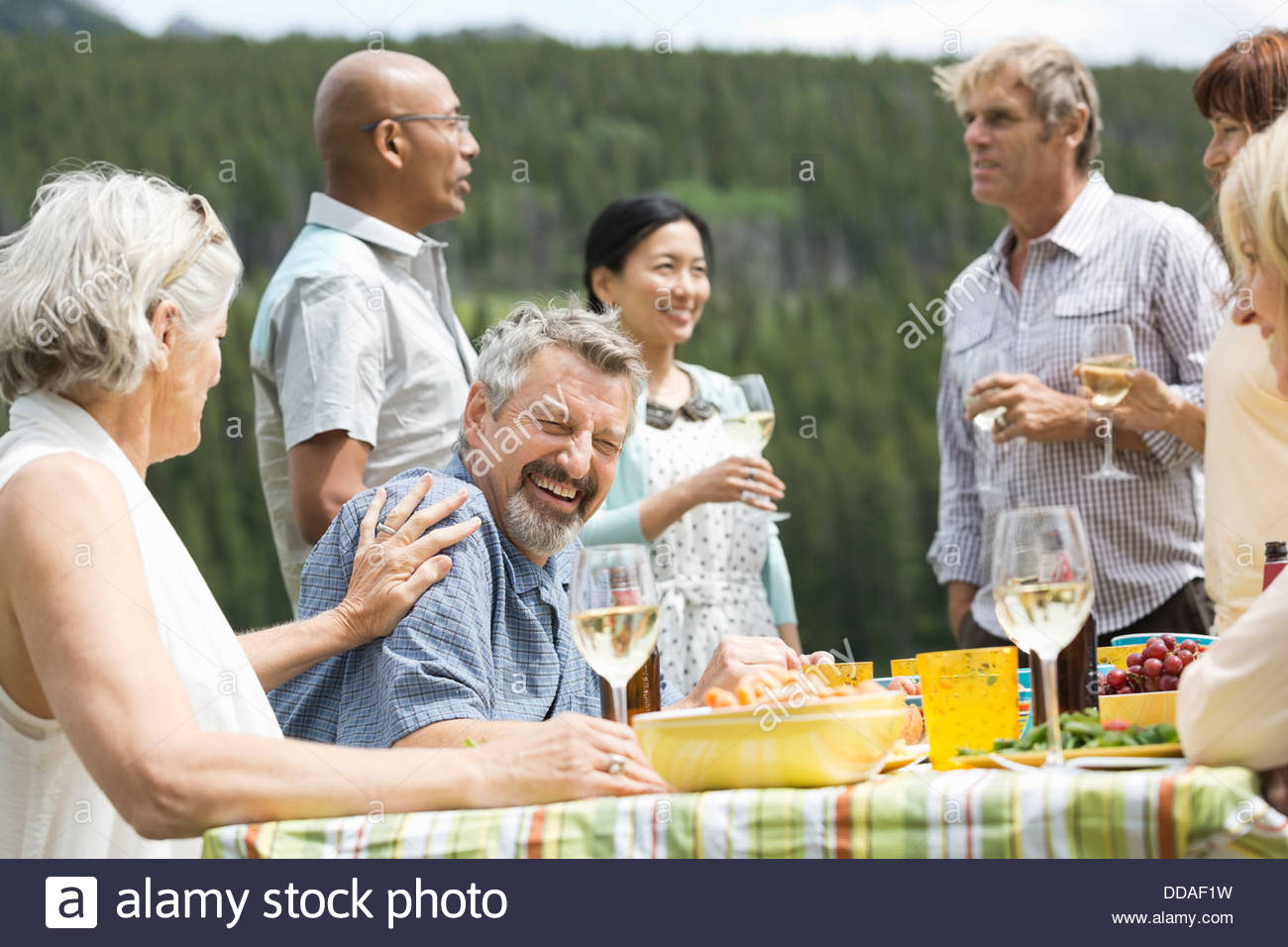 Mature couple goofing around at an outdoor picnic - Stock Image