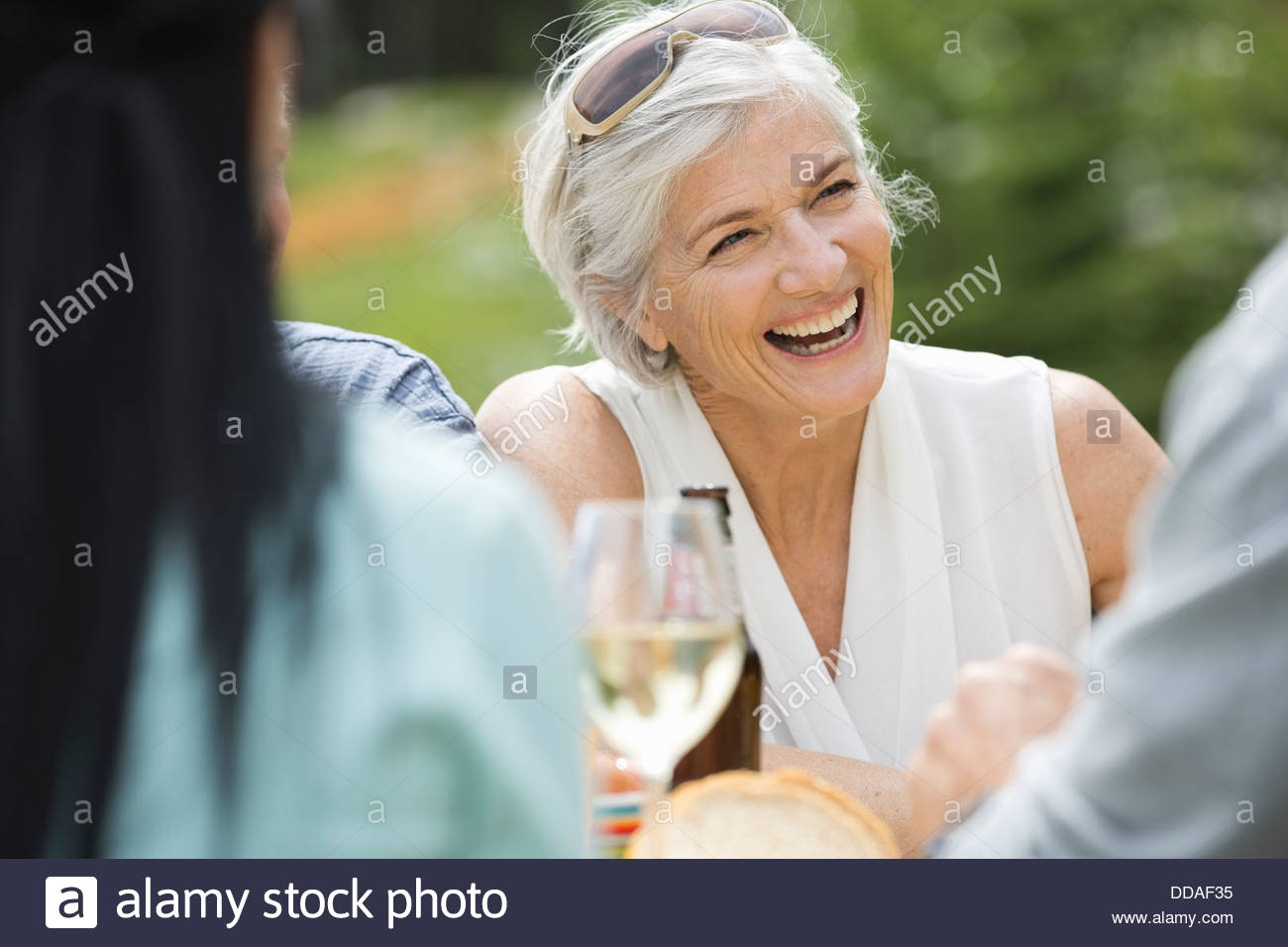 Mature woman smiling among friends - Stock Image