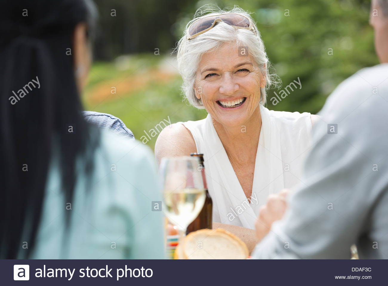 Mature woman smiling outdoors among friends - Stock Image