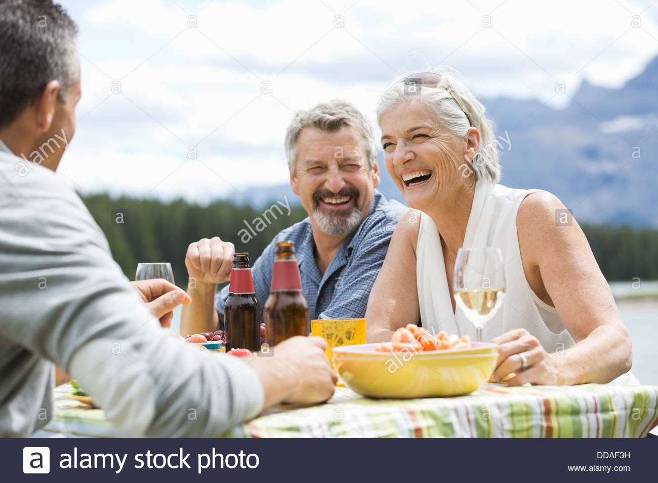 Happy couple enjoying outdoor picnic with friends - Stock Image