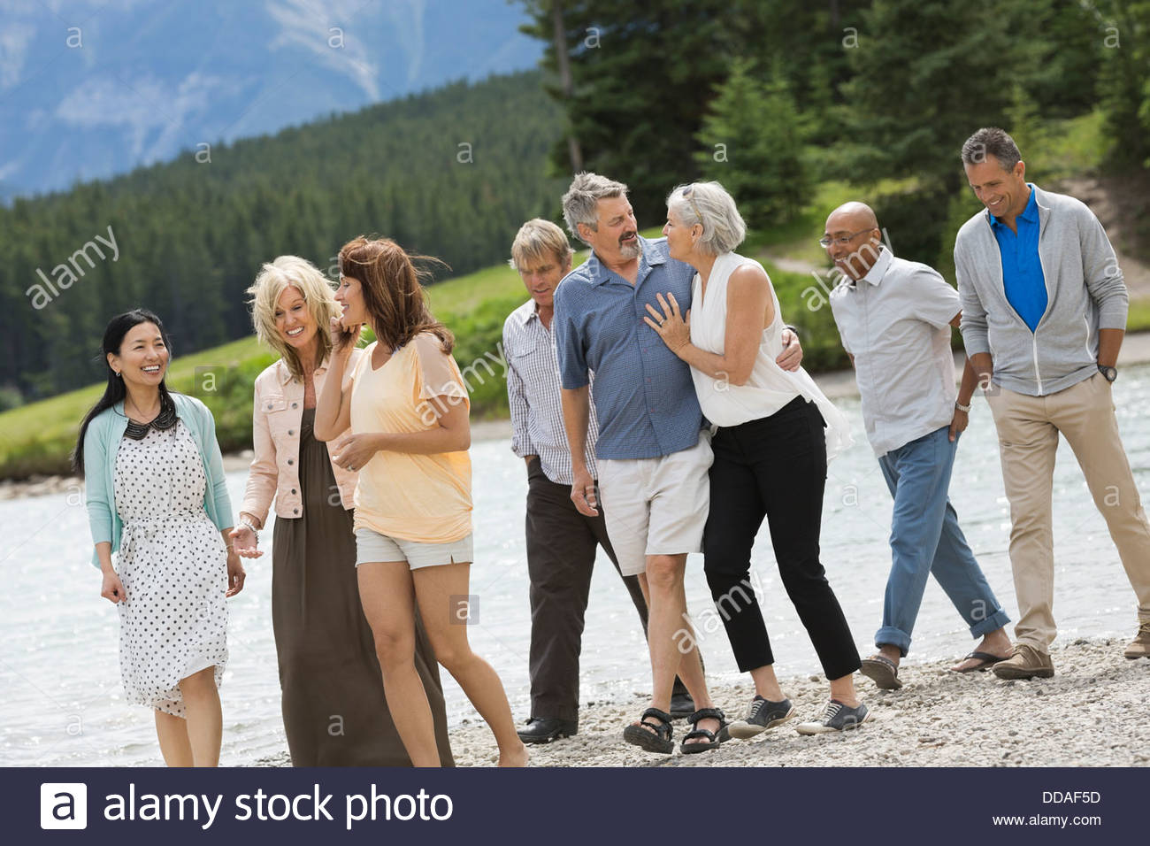 Mature group of friends walking on the beach - Stock Image