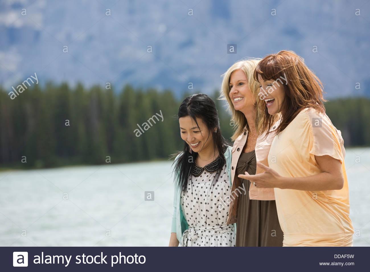 Mature female friends walking along the beach - Stock Image