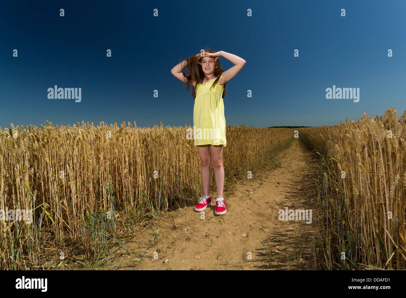 young girl looking around in the open countryside - Stock Image