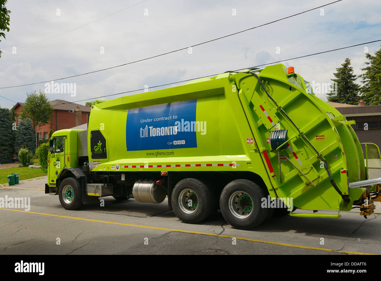 Green garbage and recycling truck on pick up day on a street in Toronto Stock Photo