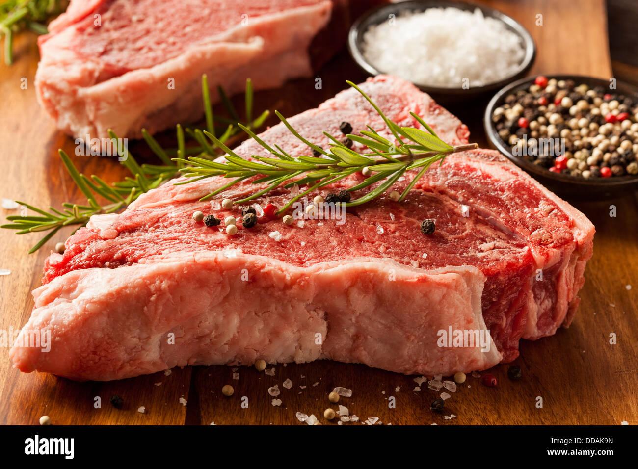 Thick Raw T-Bone Steak with Seasoning and Rosemary - Stock Image