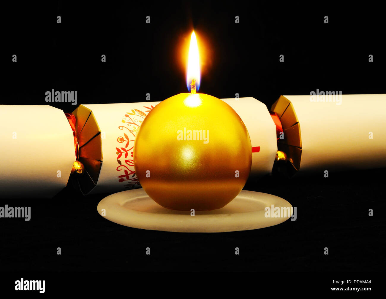 Round gold Christmas candle with a white Christmas cracker set against a black background. Stock Photo
